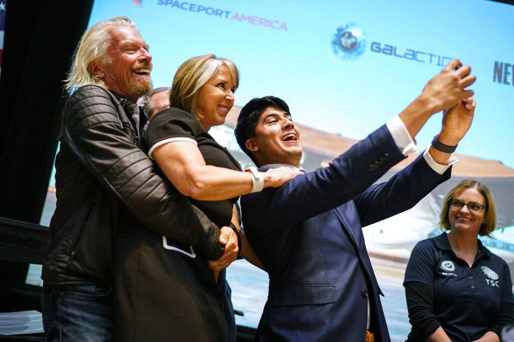 Sir Richard Branson, Gov. Michelle Lujan Grisham, and Kevin Prieto celebrate Virgin Galactic's move to New Mexico