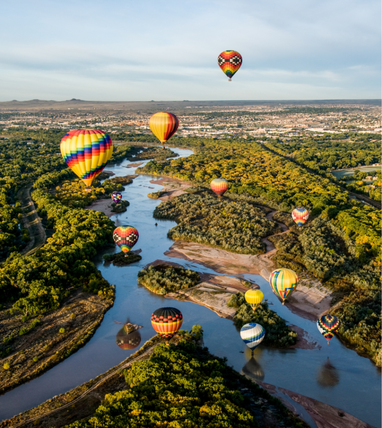 Balloons over the river. Balloon fiesta is an example of economic development in New Mexico.